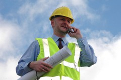an architect with blueprints, conversing on a cellular phone