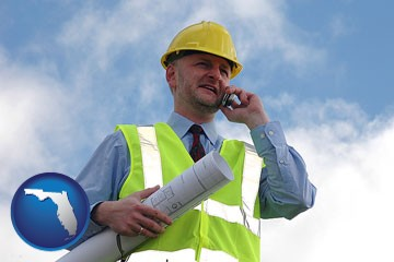 an architect with blueprints, conversing on a cellular phone - with Florida icon