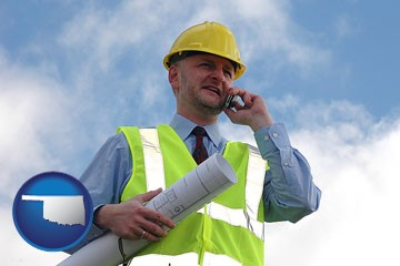 an architect with blueprints, conversing on a cellular phone - with Oklahoma icon