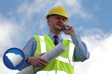 an architect with blueprints, conversing on a cellular phone - with South Carolina icon