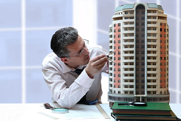 an architect studying a 3d architectural model